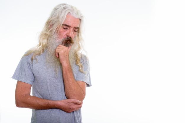 Homme barbu senior triste pensant tout en regardant vers le bas
