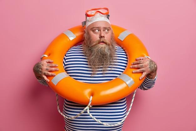Homme barbu sérieux avec bonnet de bain et lunettes, regarde ailleurs, porte un gilet de marin rayé, passe activement les vacances d'été, pose contre le mur rose. sauveteur en service. repos de plage de sécurité