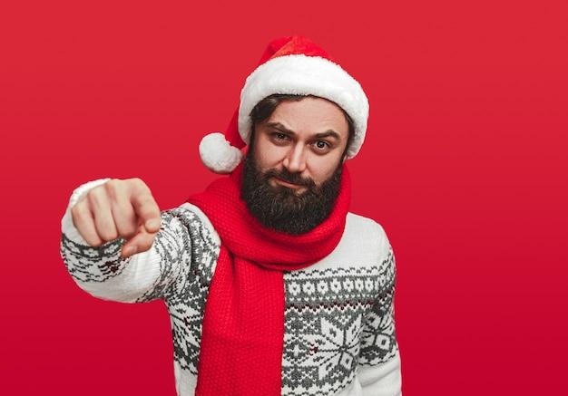 Homme barbu sérieux en bonnet de noel pointant