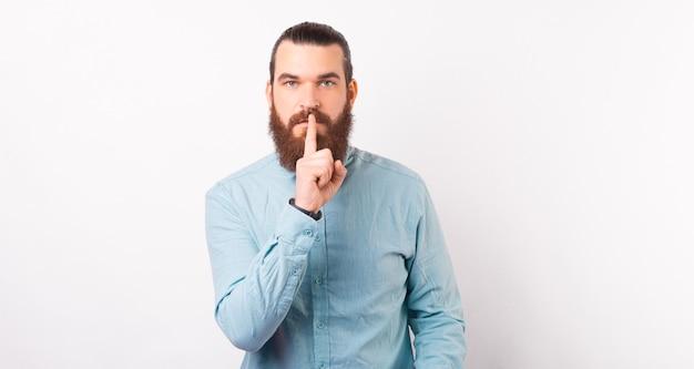 Un homme barbu sérieux fait le geste chut sur fond blanc.
