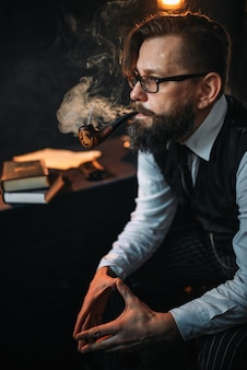 Homme barbu sérieux à lunettes pipe