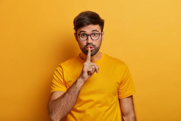 Un homme barbu silencieux garde son doigt sur les lèvres, fait un geste silencieux