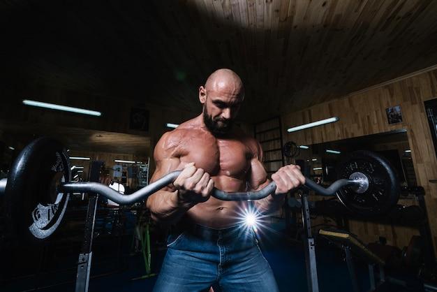 Homme barbu soulevant des haltères pendant l'entraînement