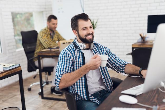 Homme barbu souriant, assis sur une chaise de bureau.