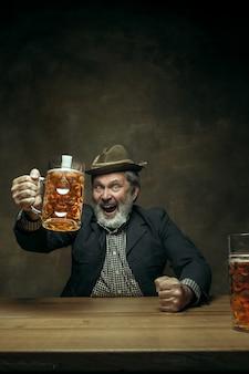Homme barbu souriant, boire de la bière au pub