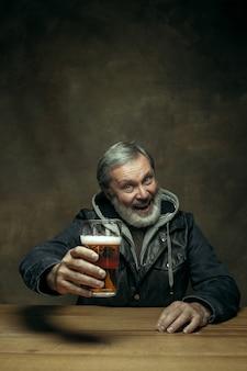 Homme barbu souriant, boire de la bière dans un pub
