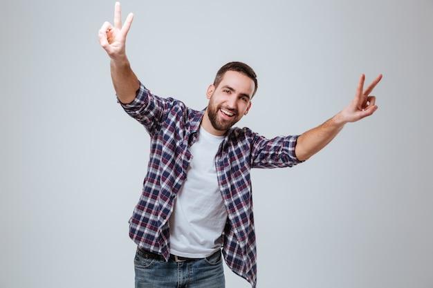 Homme barbu souriant en chemise montrant des signes de paix