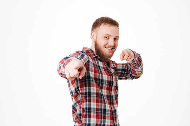 Homme barbu souriant en chemise pointant à l'avant