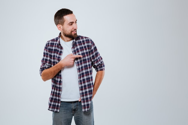Homme barbu souriant en chemise pointant loin