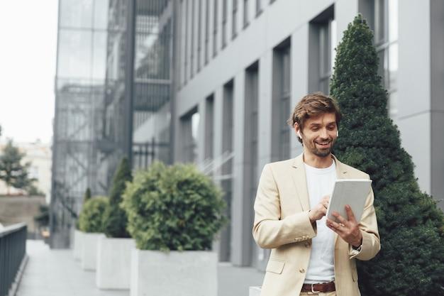 Homme barbu souriant en costume d'affaires ayant une vidéoconférence sur tablette numérique tout en se tenant près d'un immeuble de bureaux