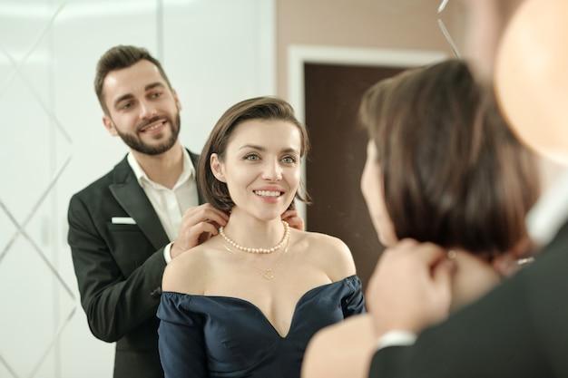 Homme Barbu Souriant En Costume Portant Un Collier à Sa Petite Amie Devant Un Miroir Pendant Qu'ils S'habillent Pour Le Dîner Au Restaurant Photo Premium