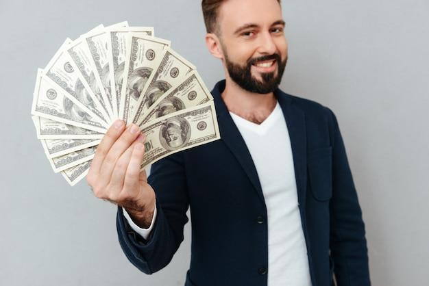 Homme barbu souriant dans des vêtements busines montrant de l'argent et regardant la caméra sur gris