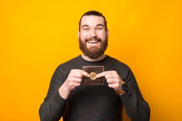 Homme barbu souriant debout sur un mur jaune et montrant des bitcoins près de portefeuille
