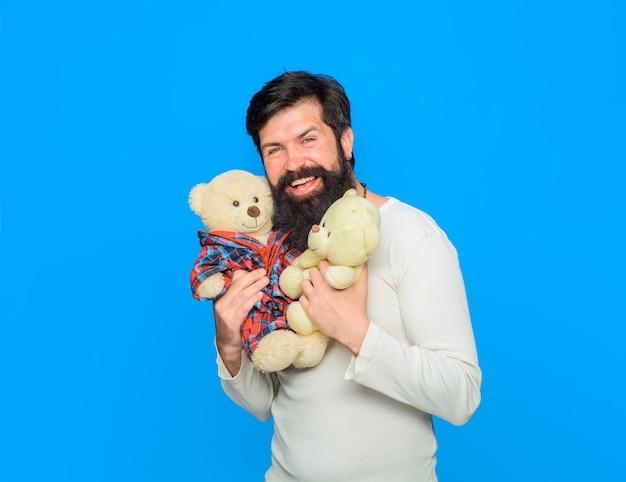 L'homme barbu souriant embrasse l'homme ours en peluche détient des ours en peluche en peluche anniversaire célébration de vacances