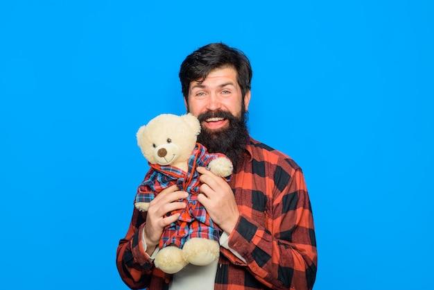 Un homme barbu souriant embrasse l'homme ours en peluche avec un ours en peluche, un anniversaire ou un anniversaire en peluche