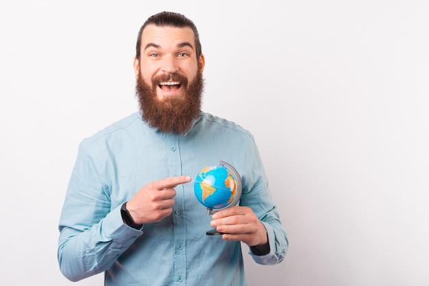 Un homme barbu souriant et excité tient et pointe du doigt un petit globe terrestre.