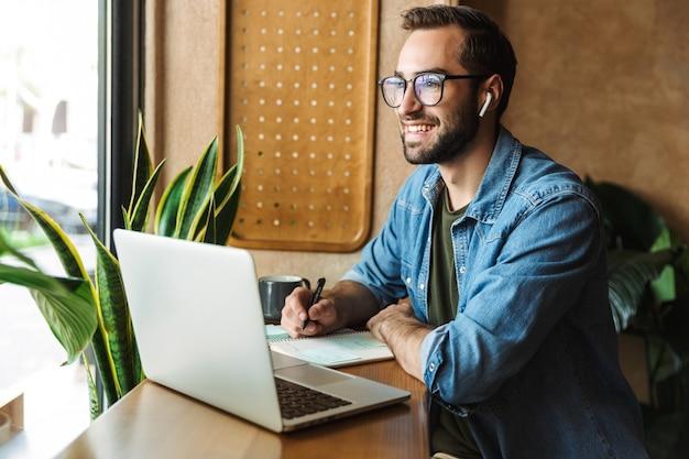 Homme barbu souriant portant des lunettes, écrivant des notes et utilisant un ordinateur portable tout en travaillant dans un café à l'intérieur