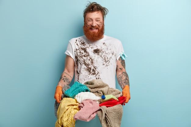 Homme barbu souriant positif heureux presque de finir les travaux ménagers, a des vêtements sales