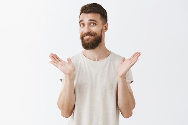 Homme barbu souriant réticent posant contre le mur blanc