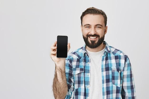 Homme barbu souriant satisfait montrant l'écran du smartphone, promotion de l'application