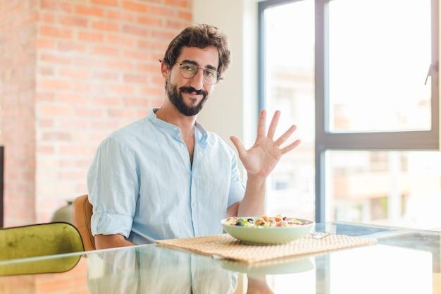 Homme barbu souriant et à la sympathique, montrant le numéro cinq ou cinquième avec la main vers l'avant, compte à rebours