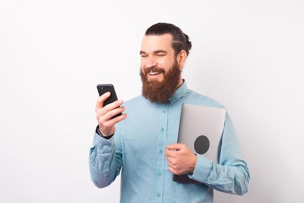 Un homme barbu souriant utilise son téléphone tout en tenant un ordinateur portable.