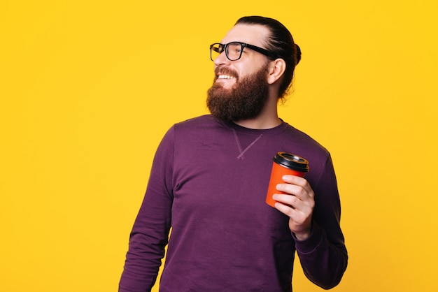 Homme barbu sourit et regarde ailleurs portant des lunettes tient une tasse de boisson chaude