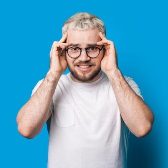 Homme barbu stressé aux cheveux blonds et lunettes touchant sa tête sur un mur de studio bleu