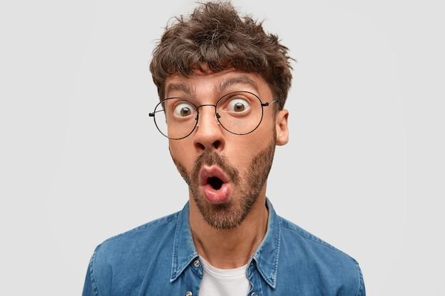 Un homme barbu stupéfait, choqué, laisse tomber la mâchoire, regarde avec des yeux écarquillés, se demande les dernières nouvelles sur un ami proche, ne peut pas croire à sa maladie grave, isolé sur un mur blanc