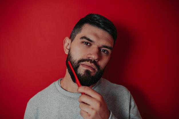 Homme barbu sur la surface rouge, sexy homme barbu, homme se peignant la barbe sur le fond rouge,