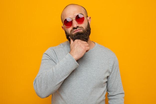 Homme barbu en sweat-shirt gris portant des lunettes rouges en levant la main sur son menton pensant