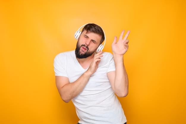 Un homme barbu en t-shirt blanc et avec des écouteurs sur les oreilles danse au rythme de la musique.