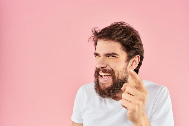 Homme barbu en t-shirt blanc gesticulant avec l'expression du visage des mains bouchent rose.