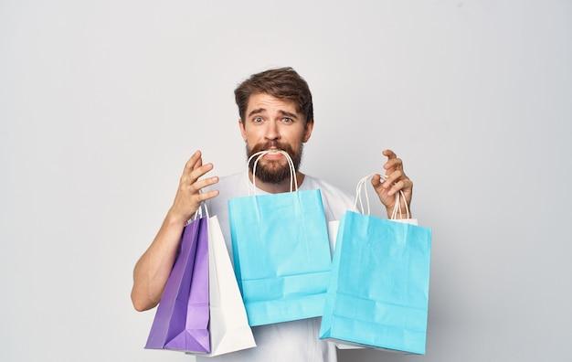 Homme barbu en t-shirt blanc avec des paquets en mains shopping vacances