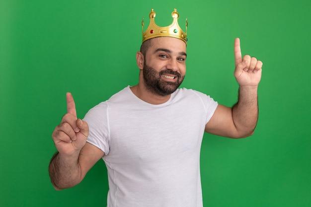 Homme barbu en t-shirt blanc portant une couronne d'or pointant heureux et positif avec l'index debout sur le mur vert
