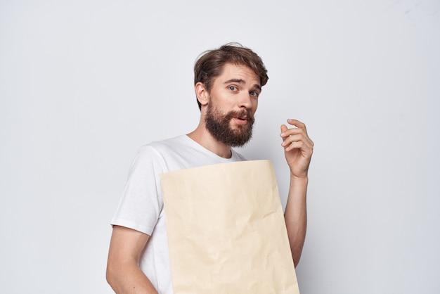 Homme barbu en t-shirt blanc sac kraft paquet d'achats. photo de haute qualité