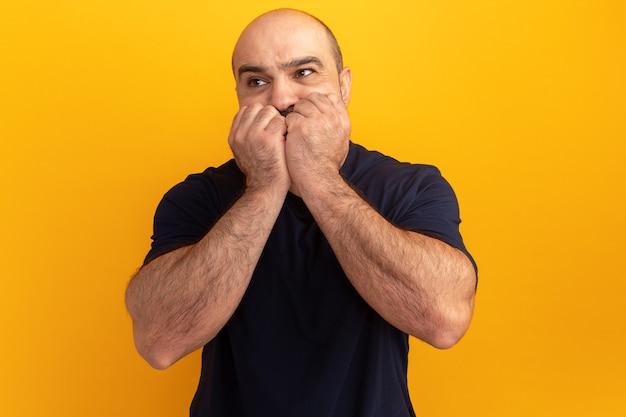 Homme barbu en t-shirt bleu marine à côté stressé et nerveux se mordant les ongles debout sur un mur orange