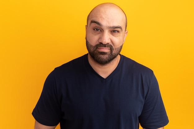 Homme barbu en t-shirt bleu marine avec visage sérieux debout sur un mur orange