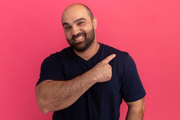 Homme barbu en t-shirt marine souriant joyeusement pointant vers l'arrière debout sur un mur rose