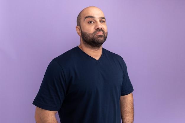 Homme barbu en t-shirt marine avec visage sérieux debout sur un mur violet
