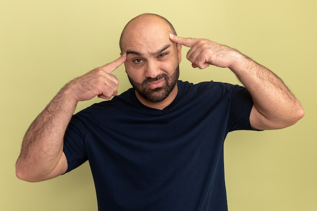 Homme barbu en t-shirt noir confus pointant avec l'index sur ses tempes pour erreur debout sur mur vert