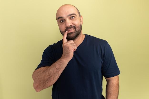 Homme barbu en t-shirt noir confus et surpris debout sur un mur vert