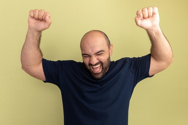 Homme barbu en t-shirt noir fou heureux et excité hurlant les poings serrés debout sur le mur vert
