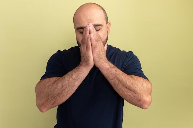 Homme barbu en t-shirt noir tenant les mains ensemble sur son visage déprimé et inquiet debout sur le mur vert
