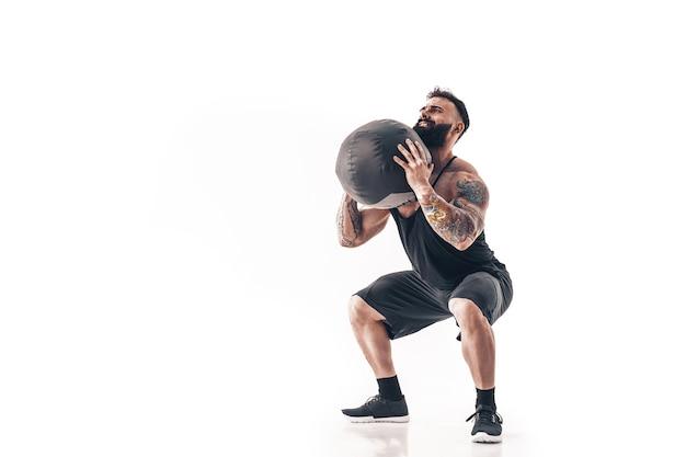 Homme barbu tatoué musclé exercice poids de remise en forme medicine ball isolé sur mur blanc.