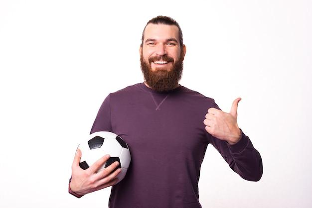 Homme barbu tenant un ballon de football et montrant un pouce vers le haut sourit à la caméra