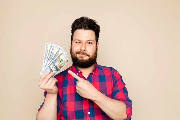 Homme barbu tenant des billets en dollars pour une campagne d'épargne financière