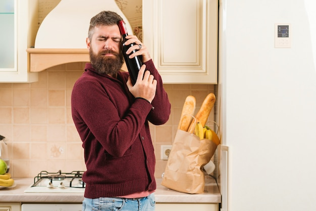 Homme barbu tenant une bouteille de vin dans la cuisine. sac d'épicerie avec de la nourriture à table. livraison de nourriture, produits à domicile. boutique en ligne avec de la nourriture, des produits et des boissons.