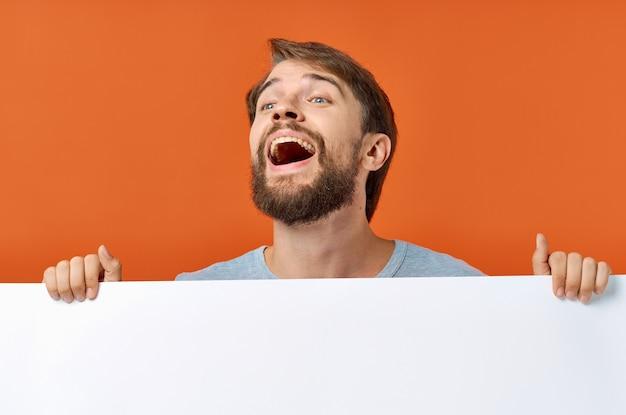 Homme barbu tenant une maquette affiche discount fond orange