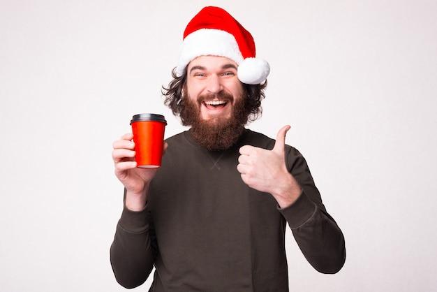 Homme barbu tenant une tasse de café pour aller et montrant le pouce vers le haut et portant un chapeau de père noël